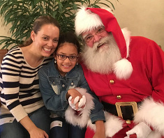 child and mom sitting with Santa