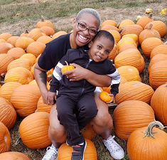 mom and son in pumpkin patch