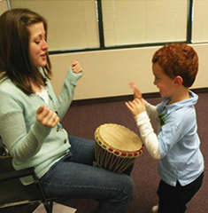 mother and son play with drum