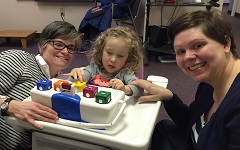 Betsy, Lekotek leader, and child play with toys